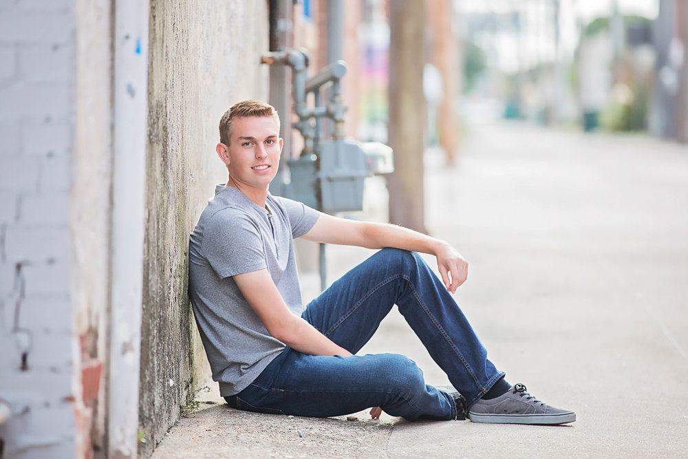 High school senior boy sitting in alley in Oklahoma City, OK.