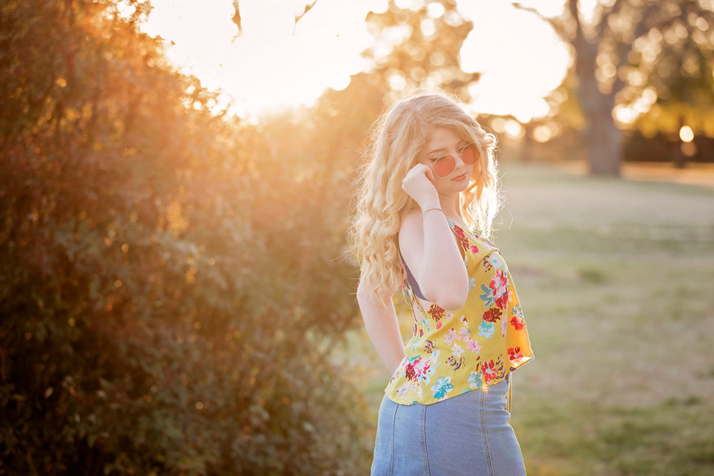 Senior girl with curly blonde hair, wearing yellow summer shirt, holding sunglass while looking down and over her shoulder at Will Rogers Park in Oklahoma City by Amanda Lynn.