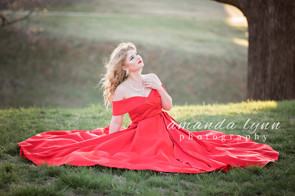 Senior girl sitting on grass, wearing red prom dress at Will Rogers Park in Oklahoma City, Oklahoma.