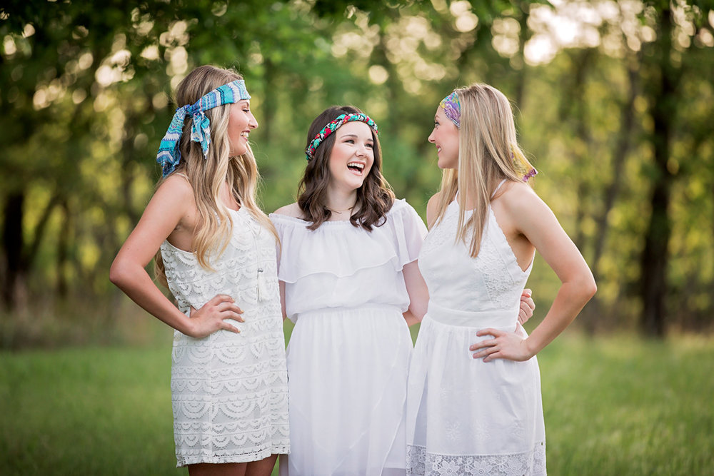 Three senior girls wearing white dresses, looking at one another and laughing at Martin Nature Park in Oklahoma City, Oklahoma.