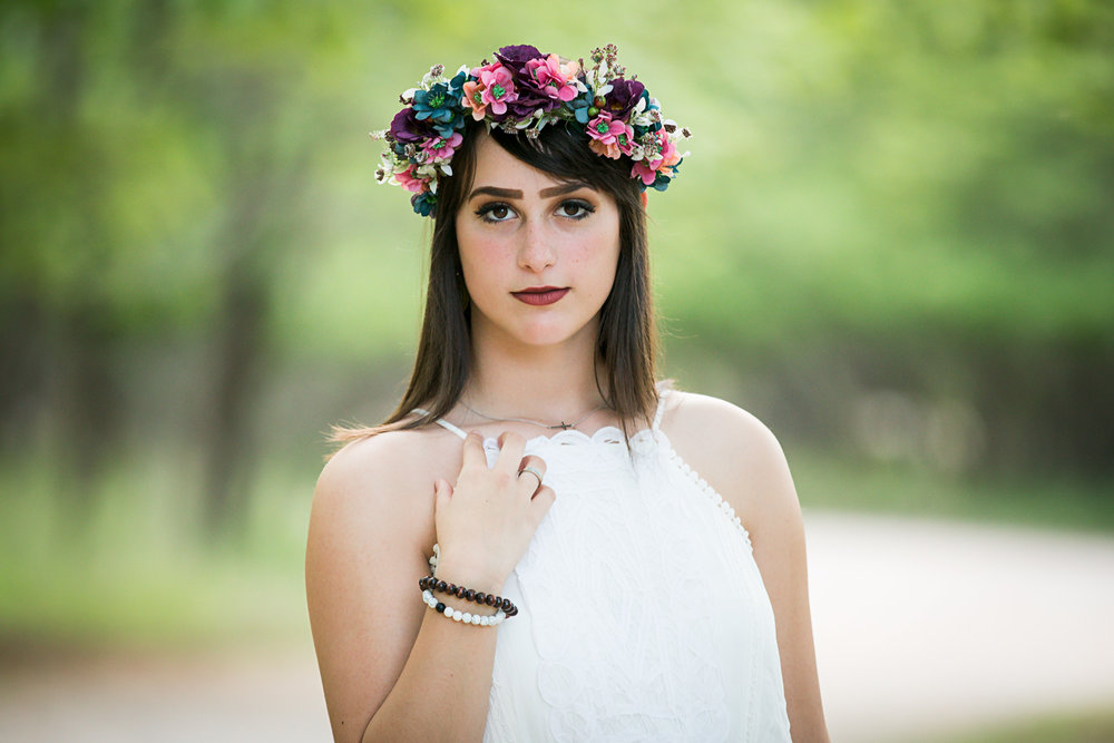Senior girl wearing floral crown and white dress, looking at camera at park in Oklahoma City.