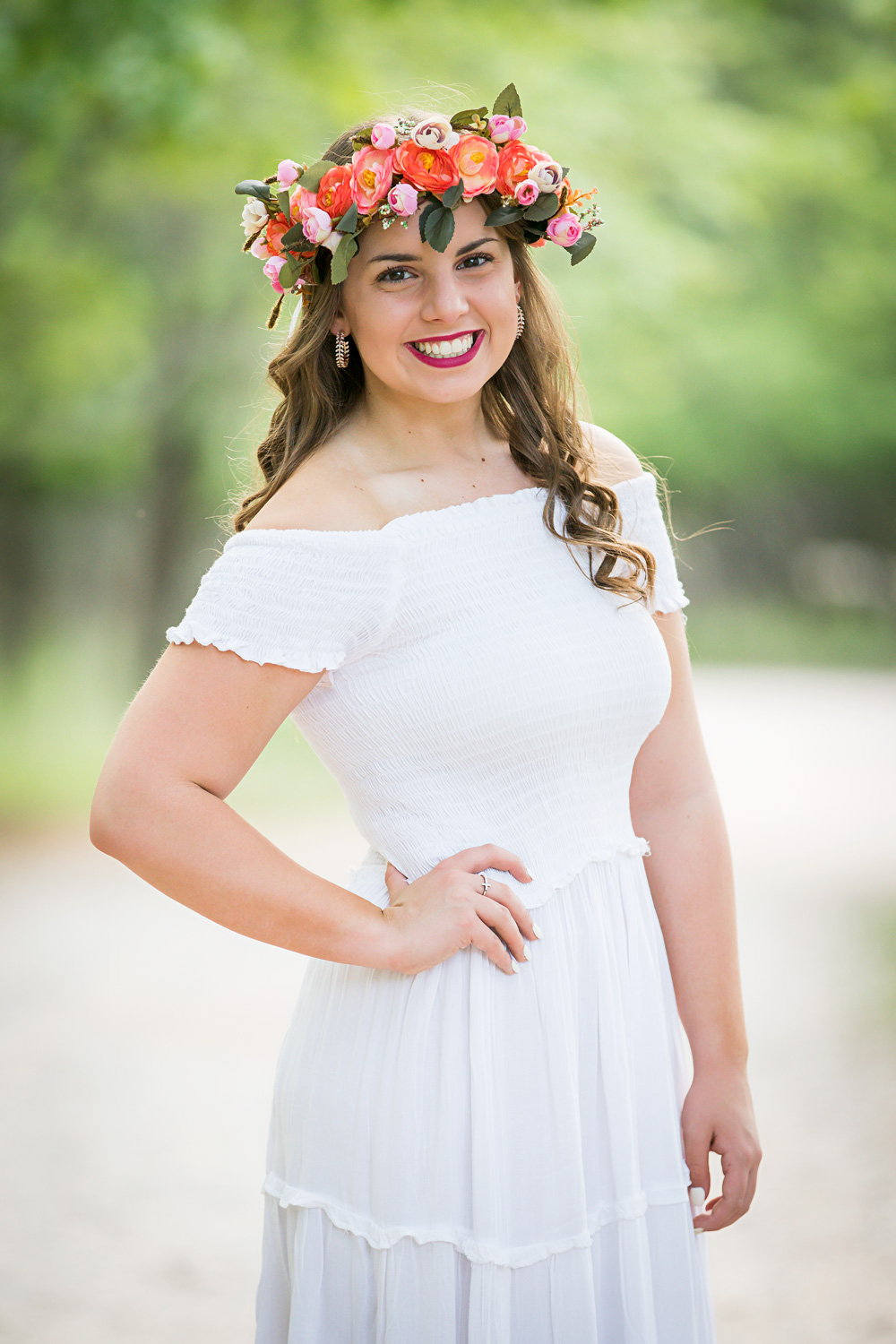 High school senior girl wearing white dress and pink and orange flower crown at Martin Nature Park in Oklahoma City.