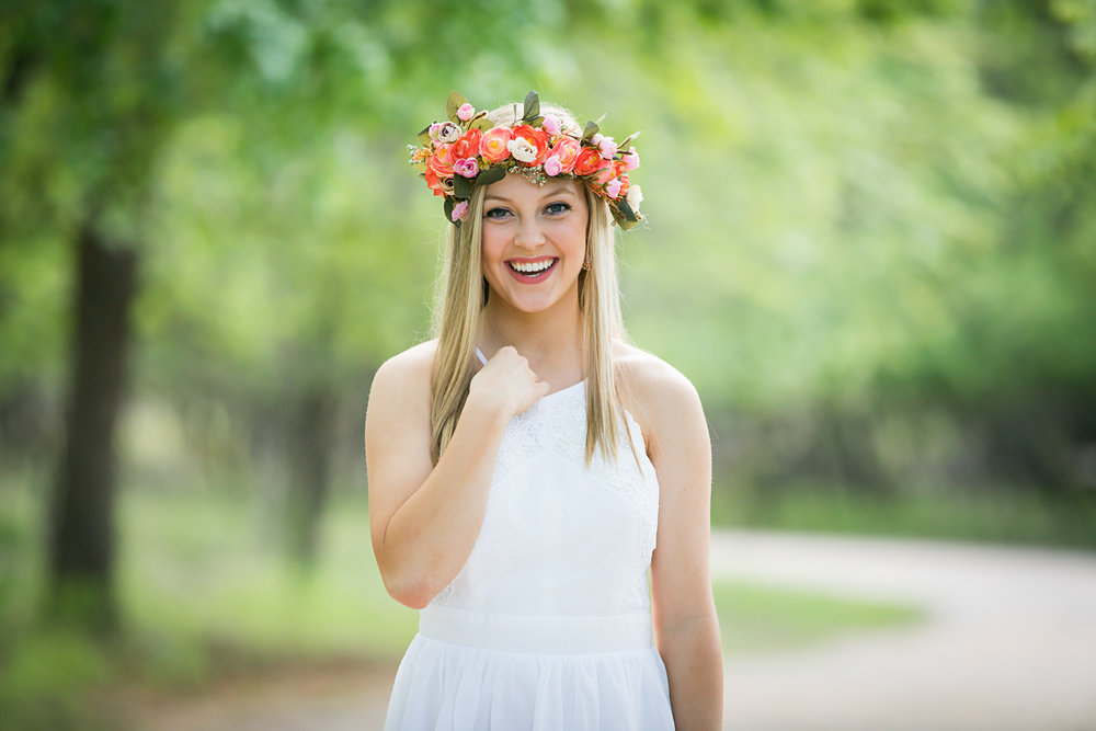 Senior girl wearing white dress, laughing and looking at camera at park in OKC.