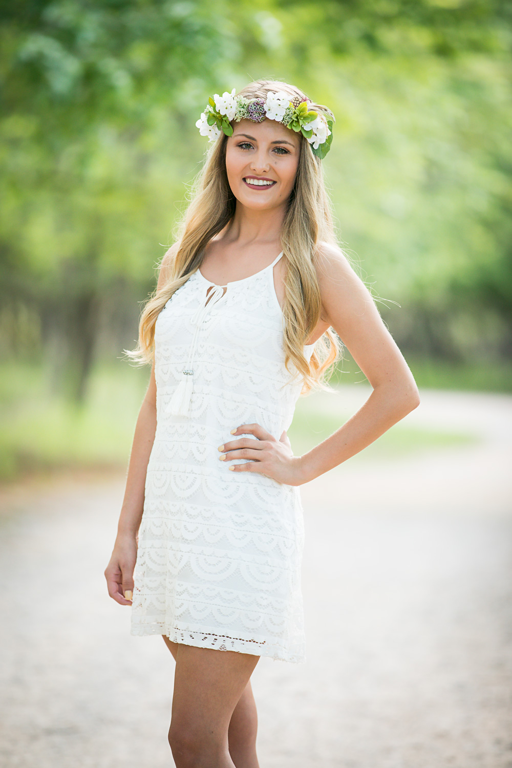 Senior girl wearing short white dress, standing with her hand placed on her hip, smiling at camera at Martin Nature Park in Oklahoma City.