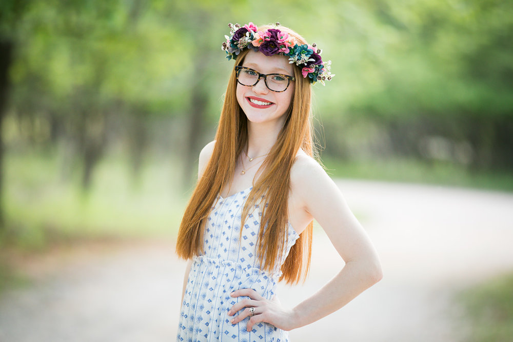 Senior girl with long red hair, wearing flower grown and summer dress at Martin Nature Park in OKC.