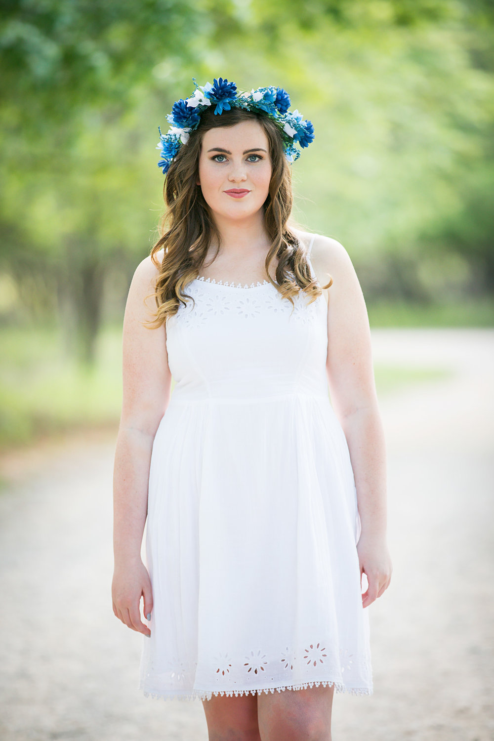High school senior girl wearing white dress and a blue flower crown, standing on road, looking at camera at Martin Nature Park in OKC.