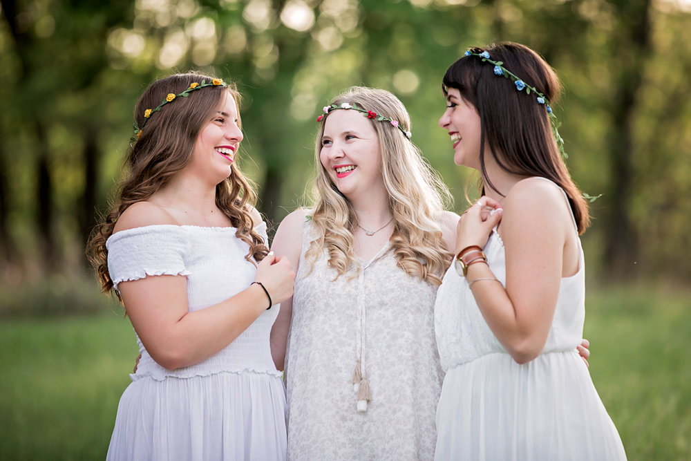 Three senior girls wearing white dresses and small flower crowns looking at one another at Martin Nature Park in Oklahoma City.