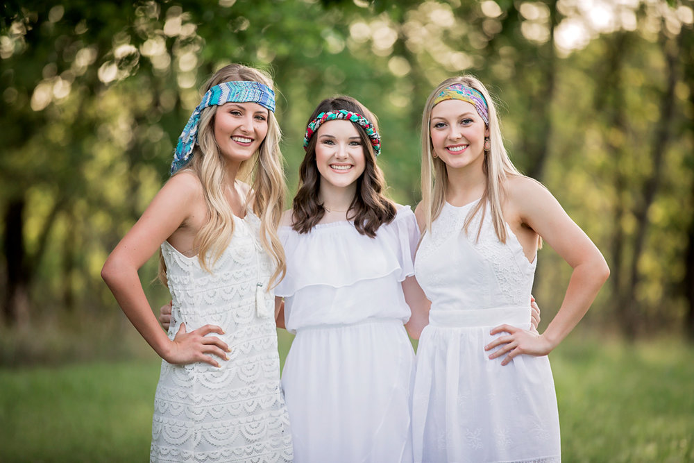 Three senior girls wearing white clothing and colorful head wraps, posing in Martin Nature Park in OKC for Amanda Lynn Photography.