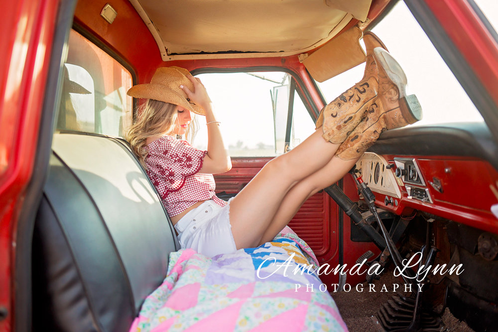 Senior girl wearing cowboy boots, sitting with feet up on dash board of old truck in Oklahoma.