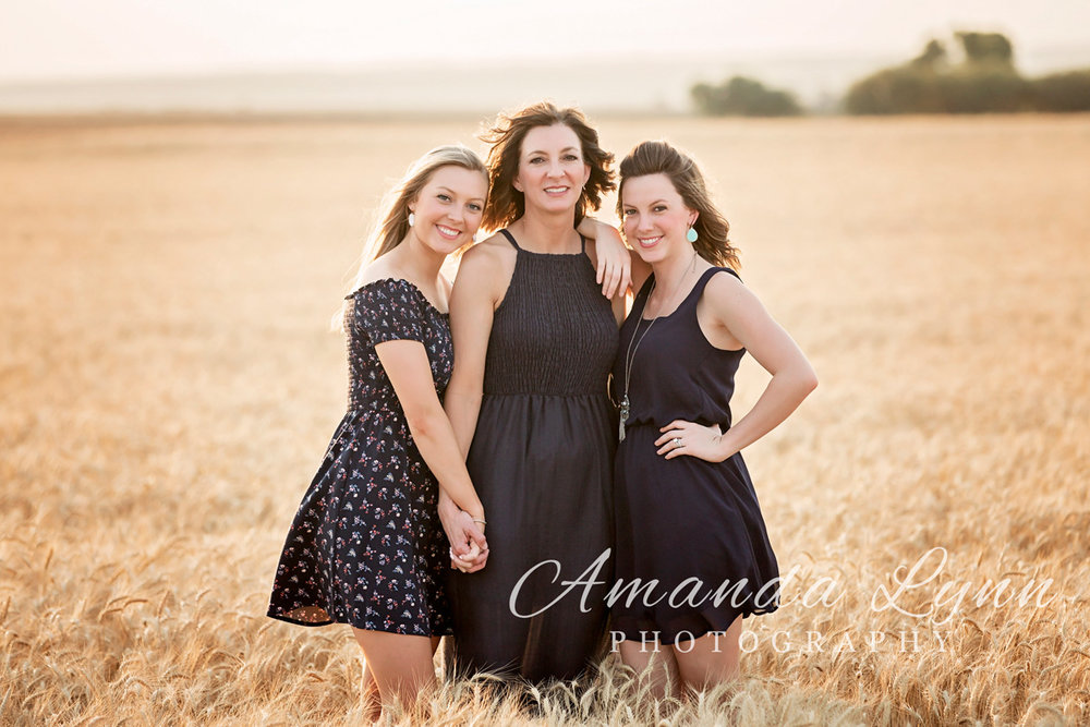 Mother with two older daughters posing for camera in middle of wheat field in western Oklahoma by Amanda Lynn.