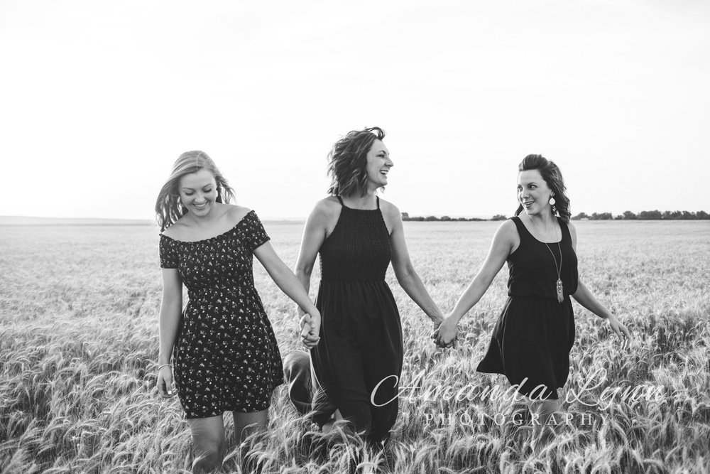 Black and white images of mother and daughters holding hands and walking through a wheat field in Oklahoma by Amanda Lynn.