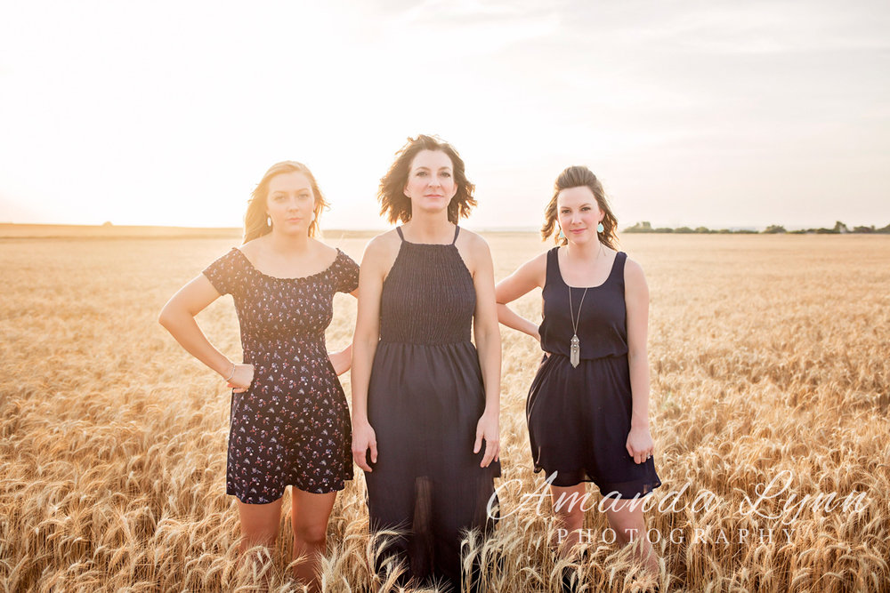 Mother with two daughters wearing blue dresses, standing in wheat field in Oklahoma.