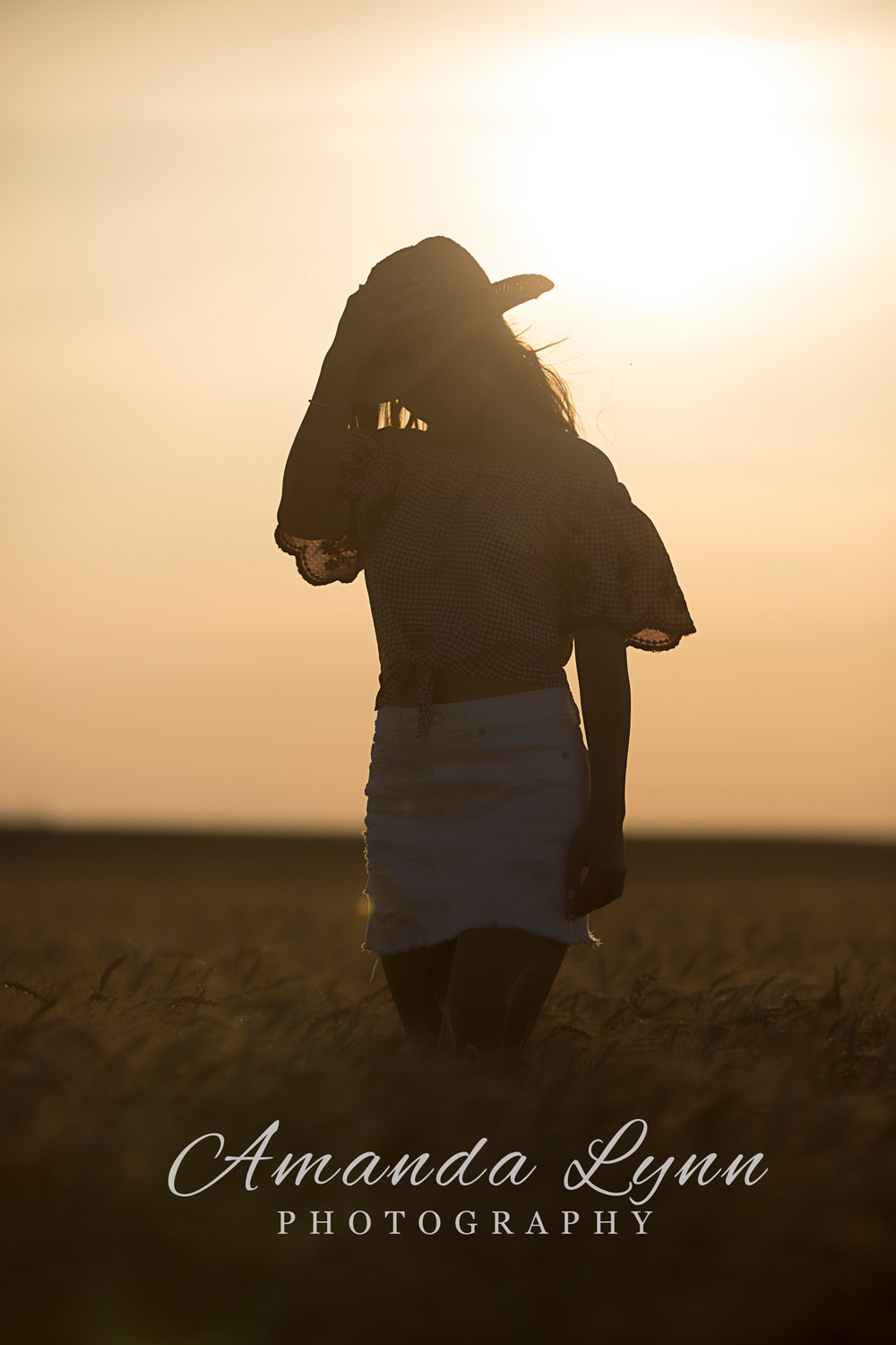 Silhouette of senior girl wearing cowboy hat in a wheat field in Oklahoma.