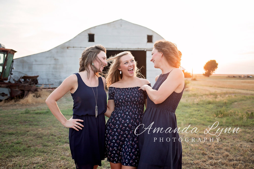 Mother and two daughters standing in front of an old barn laughing and looking at one another in western Oklahoma by Amanda Lynn Photography.