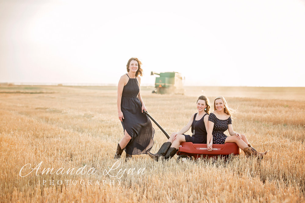 Image of mother pulling adult girls in childhood wagon through a wheat field in western Oklahoma.