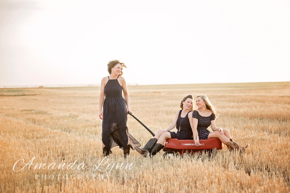 Mother wearing long blue dress, pulling adult children in childhood wagon through a wheat field in western Oklahoma by Amanda Lynn.