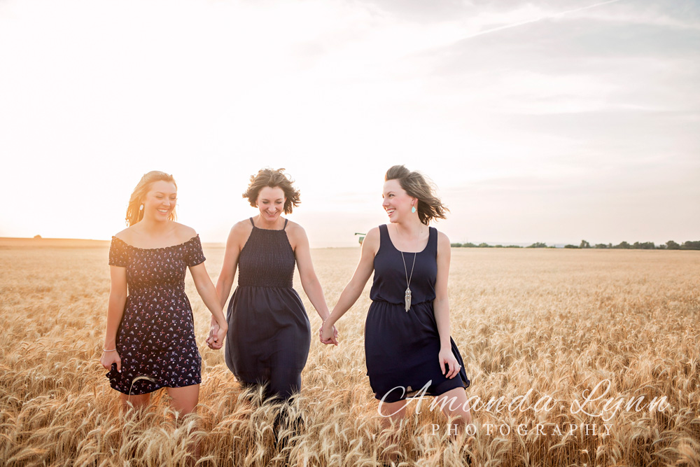 Mother and two daughters wearing blue dresses, holding hands and walking through wheat in Oklahoma.