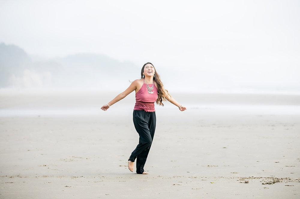 Senior girl wearing black pants and dark pink shirt, dancing on Cannon Beach by Oklahoma City Senior Photographer, Amanda Lynn.