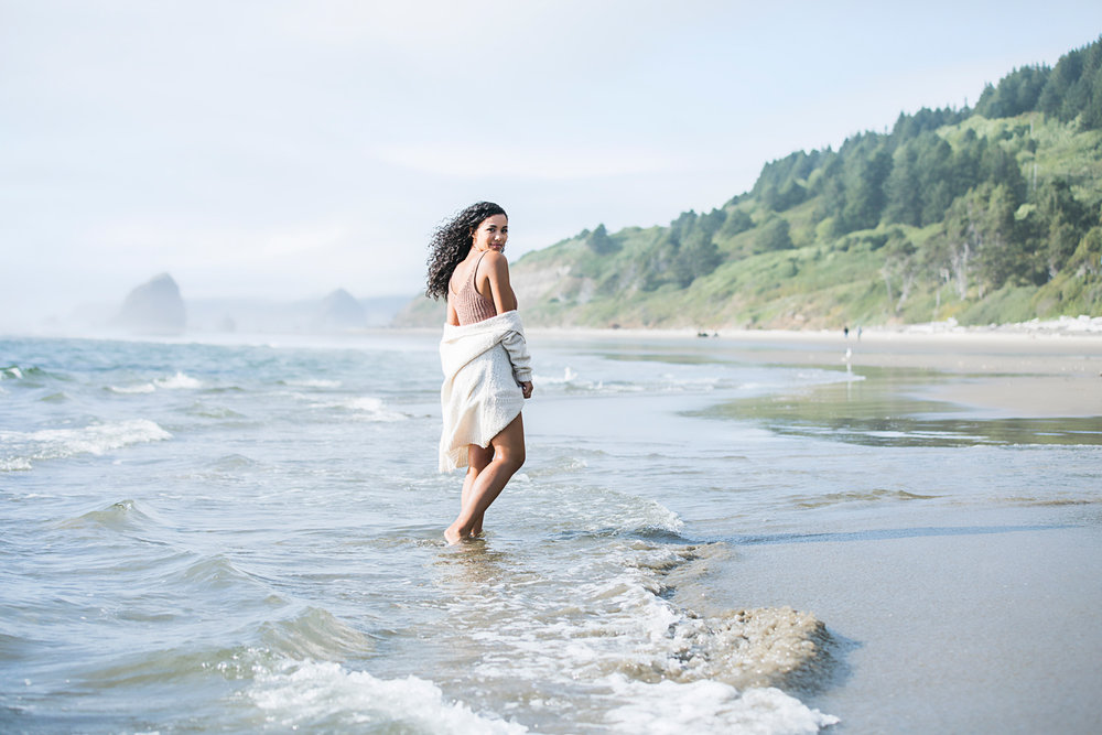 Senior girl with long brown, curly hair, standing in the ocean with long sleeve white sweater hanging off shoulder by Oklahoma City Senior Photographer Amanda Lynn.