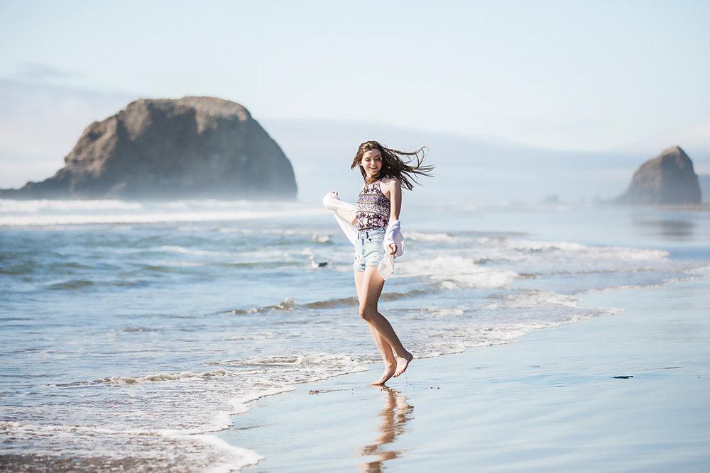 High school senior girl wearing jean shorts with white sweater, dancing in the ocean at Connon Beach, Oregon by Amanda Lynn Oklahoma City Senior Photographer.