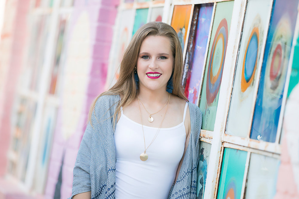 High school senior girl with long hair and bright lipstick, leaning against graffiti wall in downtown Oklahoma City by Amanda Lynn.