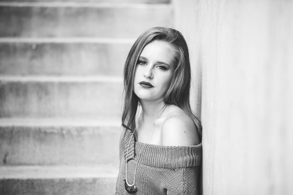 Black and white image of high school senior girl sitting on concrete steps in downtown Oklahoma City by Amanda Lynn Photography.