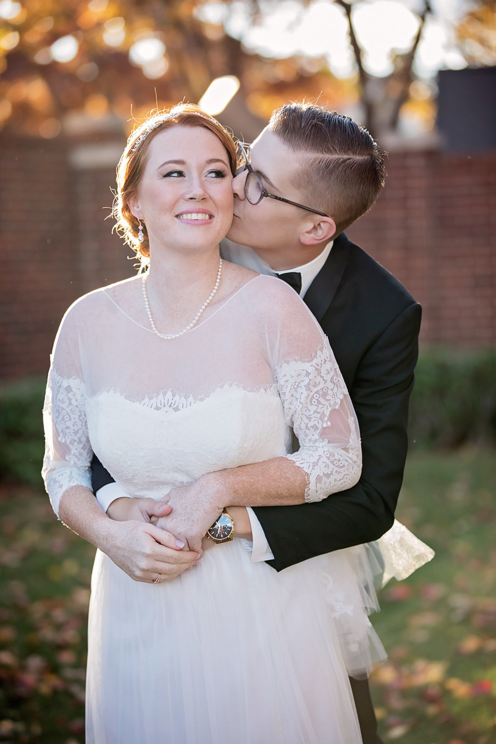 Bride and groom hugging with groom kissing bride on the cheek in Oklahoma City by Amanda Lynn.