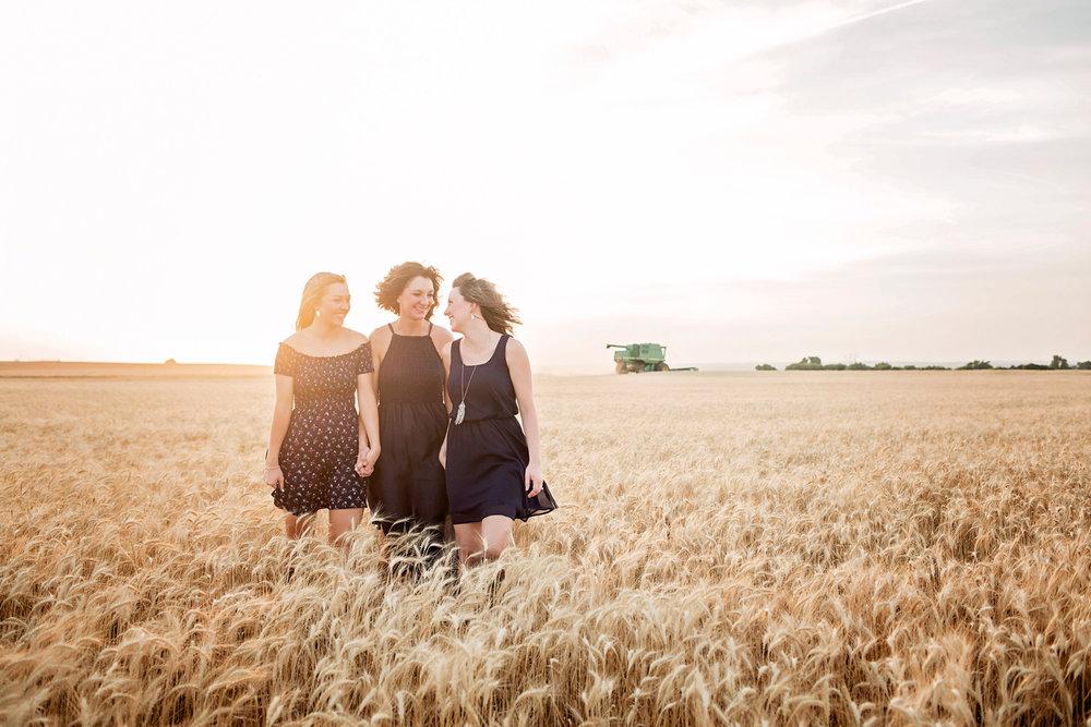 Family of three wearing blue dresses, walking in a wheat field in western Oklahoma by Amanda Lynn.