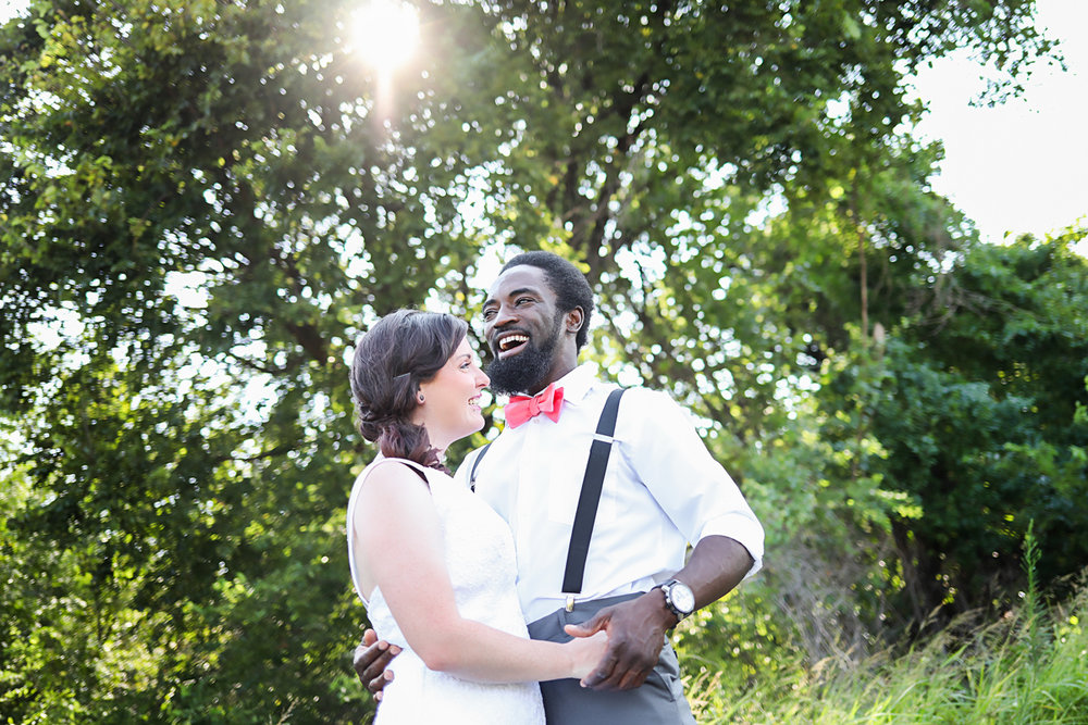Image of bride and groom laughing with beautiful sun flare above their heads at wedding in Oklahoma.