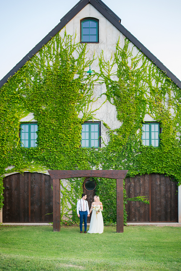 Bride and groom standing in front of beautiful building covered in ivy at the Baumberhof in Oklahoma City, OK by Amanda Lynn Photography.