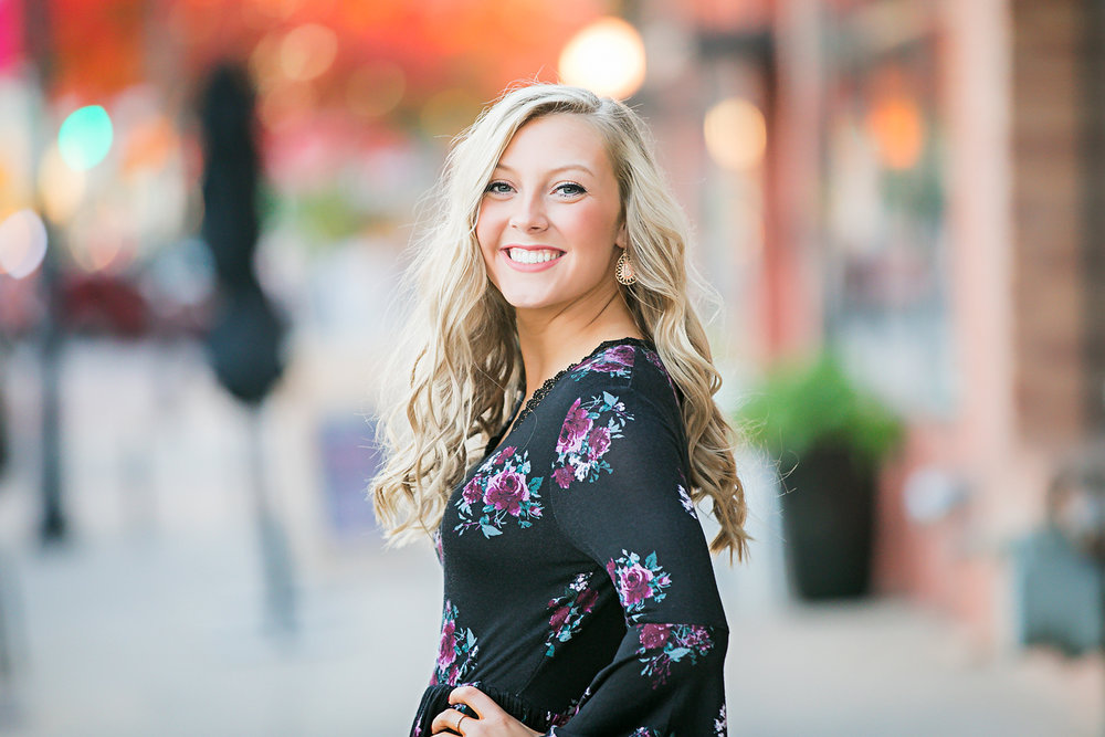 Senior girl wearing black floral top, standing on sidewalk with hand on hip in Automobile Alley in Oklahoma City by Amanda Lynn Photography.