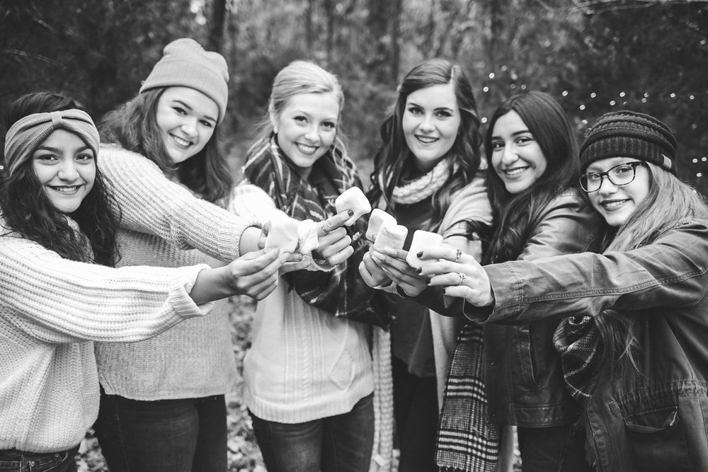 black and white image of high school senior girls holding marshmallows at camp fire in Oklahoma City by Amanda Lynn Photography.