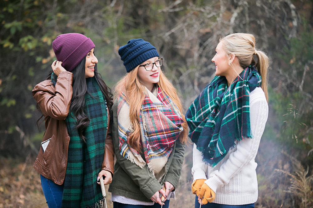 Three senior girls standing around camp fire roasting marshmallows in Oklahoma by Amanda Lynn Photography.