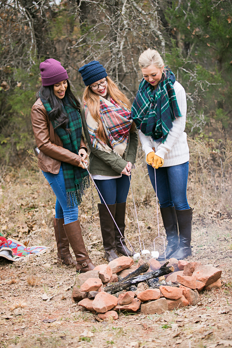Three senior girls wearing fall clothing and tall boots, standing around a camp fire, roasting marshmallows in Oklahoma by Amanda Lynn Photography.