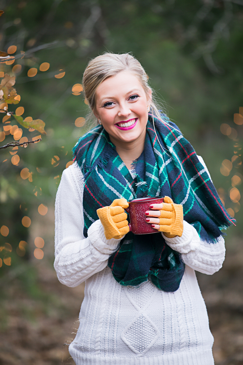 High school senior girl wearing a white sweater and blue, green scarf, holding a red coffee mug and smiling towards the camera in Oklahoma City by Amanda Lynn.