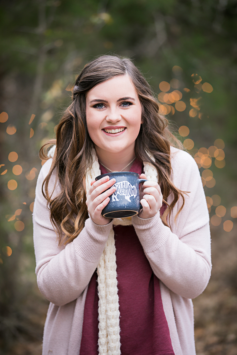 High school senior girl wearing pink and maroon, holding blue coffee cup that says Oklahoma and smiling for the camera by Amanda Lynn.