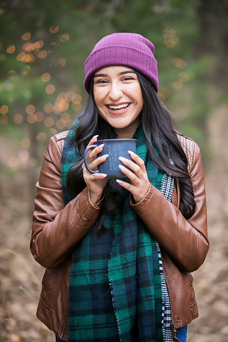 Senior girl wearing brown leather jacket and maroon stocking hat, holding coffee cup and standing in the woods in Oklahoma by Amanda Lynn Photography.
