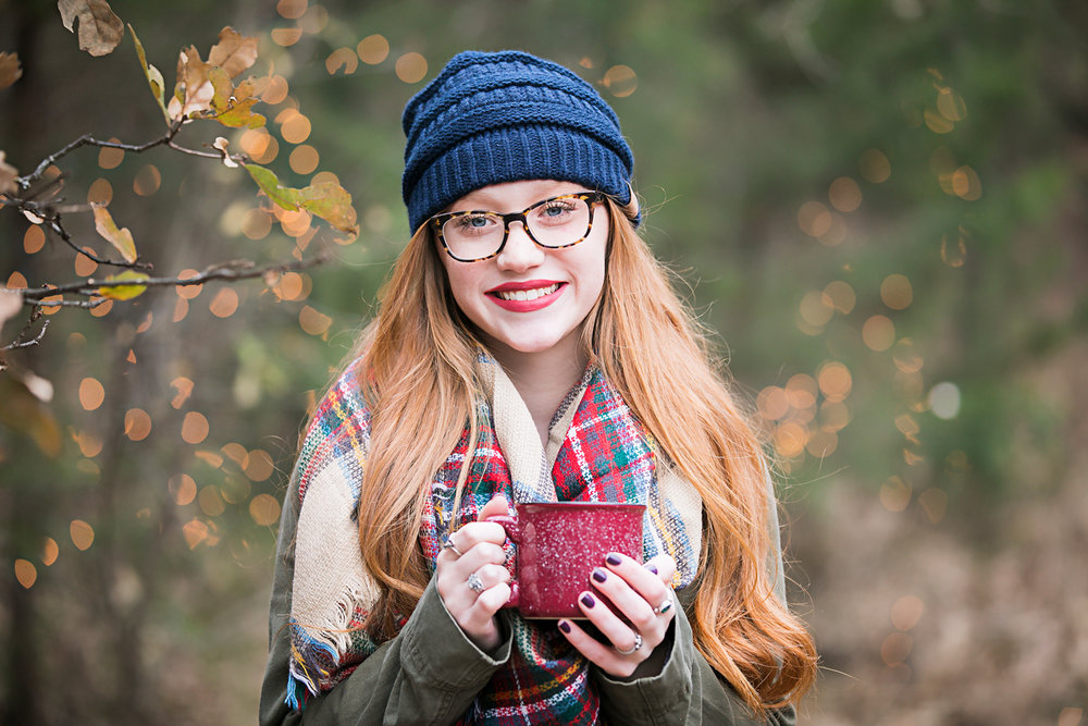 Oklahoma senior girl with long red hair, wearing a blue hat and fall colored scarf, holding coffee mug and smiling for camera in Oklahoma by Amanda Lynn Photography.