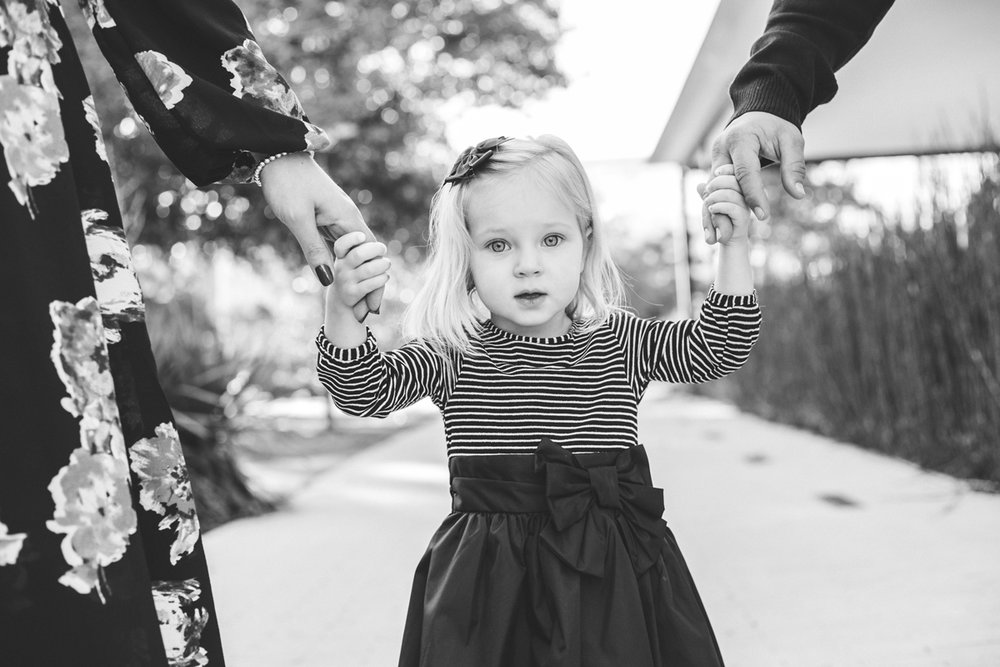 Black and white image of little girl holding her parents hands at the Myriad Gardens in OKC by Amanda Lynn.