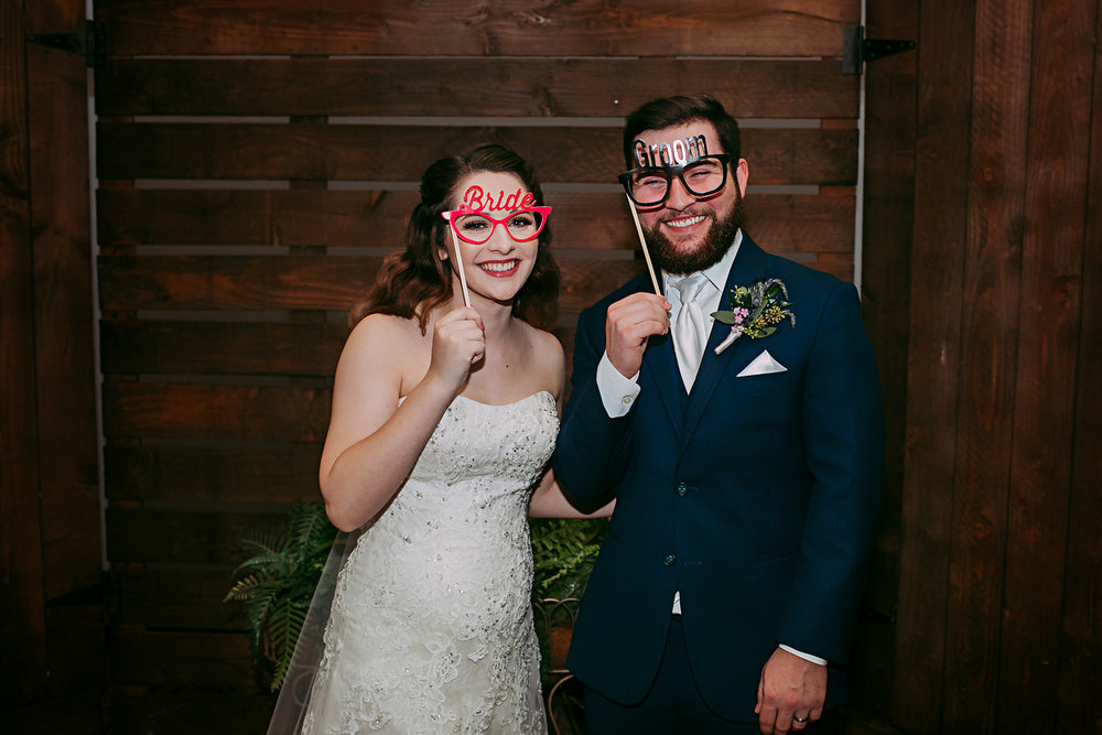 Bride and groom at using photo booth props at their wedding reception by Amanda Lynn Photography, Oklahoma.