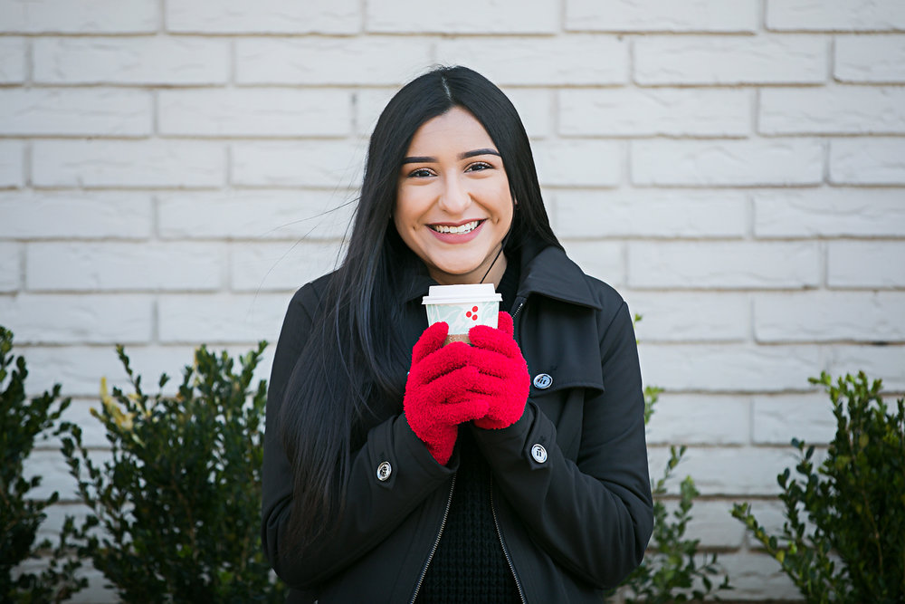 Oklahoma high school senior portrait of girl wearing black coat and red gloves, holding a coffee in the Paseo District in Oklahoma City by Amanda Lynn.