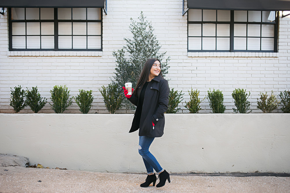 High school senior portrait of girl wearing blue jeans with black heels, black jacket and red gloves, walking in the Paseo District in OKC by Amanda Lynn.