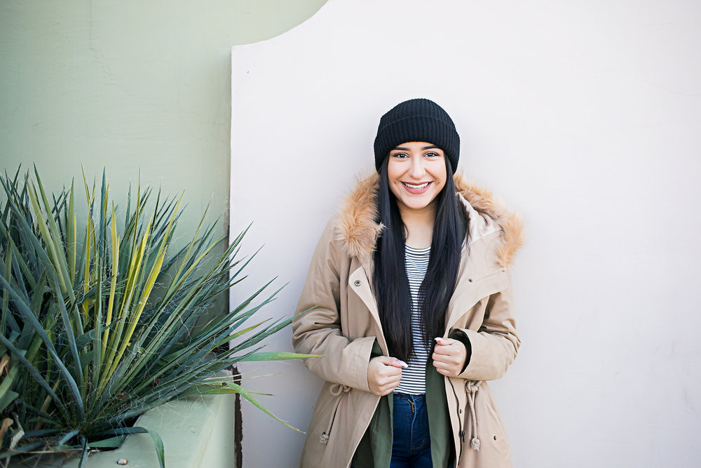 High school senior girl wearing black hat and tan jacket, leaning against wall at the Paseo District in Oklahoma City by Amanda Lynn.