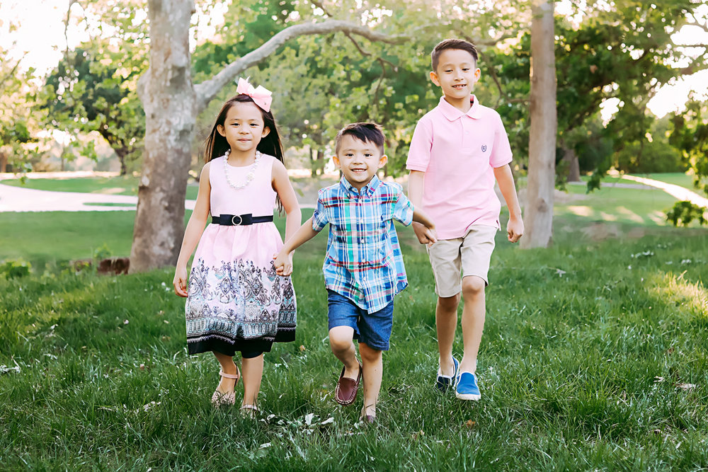 Three siblings wearing pink and blue, holding hands and running at Will Rogers Park in Oklahoma City by Amanda Lynn Photography.