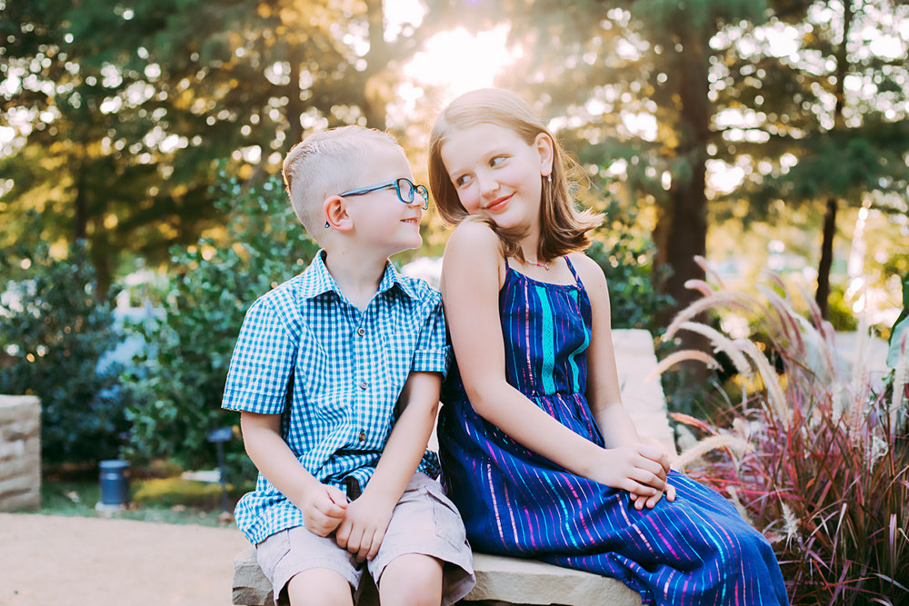 Brother and sister sitting on brick wall with sun setting behind them at the Myriad Gardens in Oklahoma City by Amanda Lynn Photography.