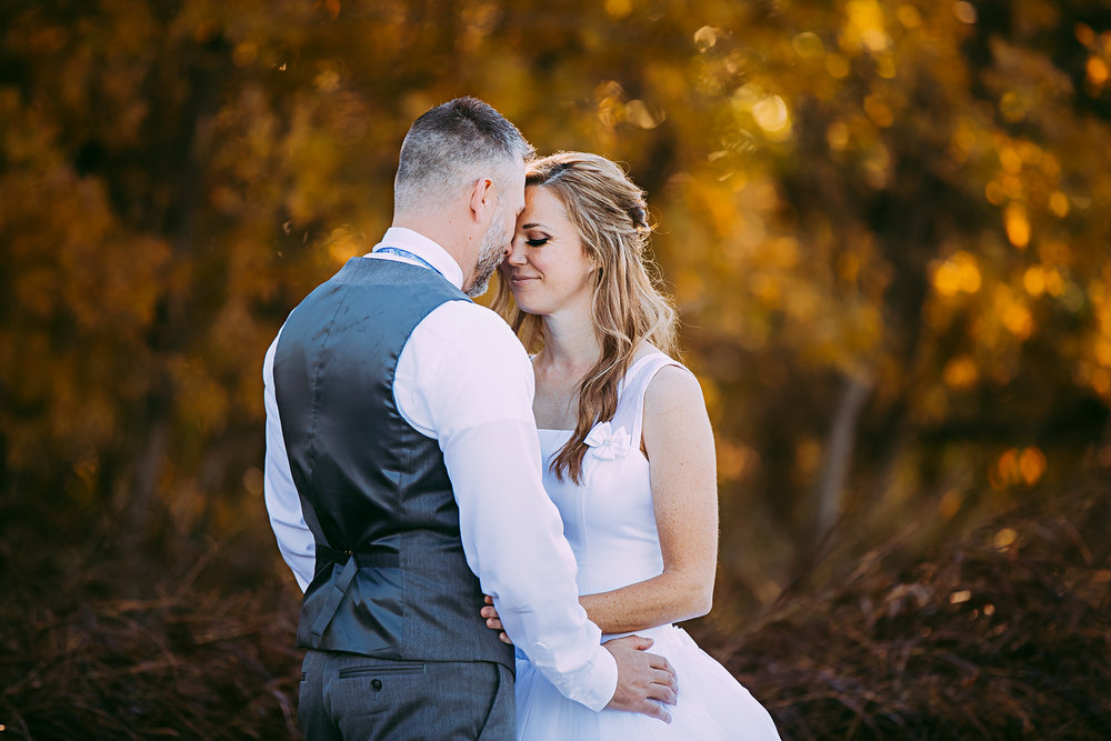Bride and groom embracing with a beautiful fall backdrop at Martin Park Nature Center in Oklahoma City by Amanda Lynn Photography.