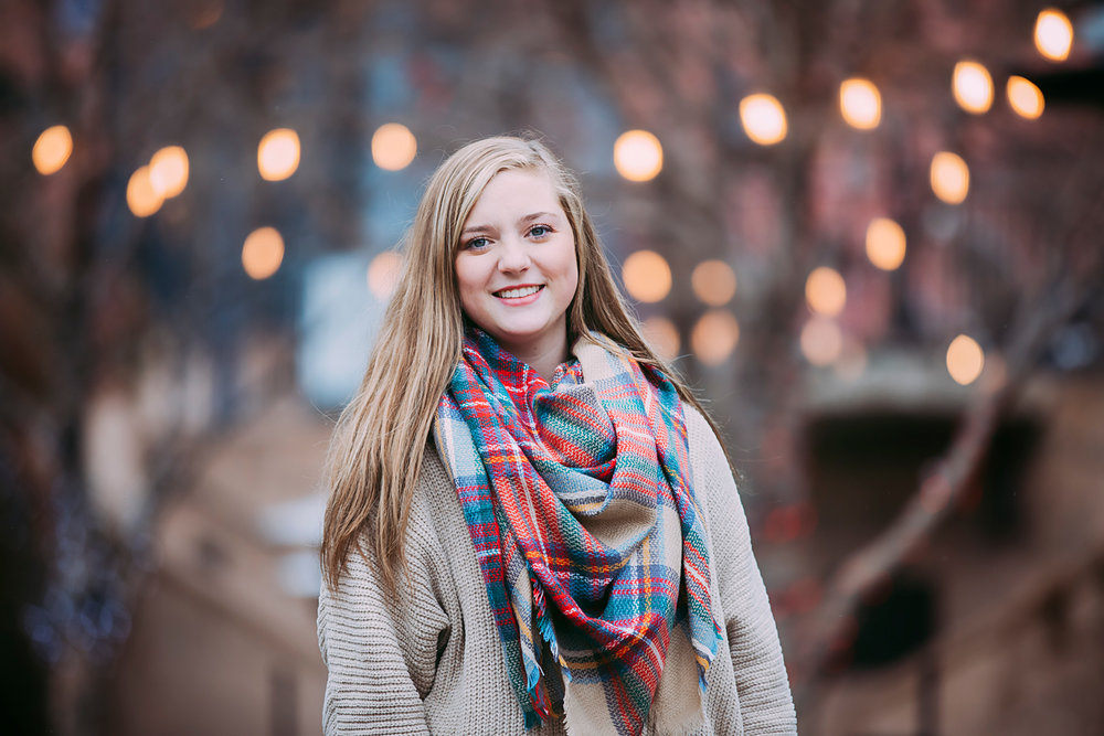 High school senior girl wearing tan sweater and scarf, standing by the brick town canal in downtown Oklahoma City by Amanda Lynn.