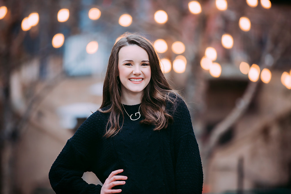 Senior girl wearing black sweater, standing in front of Christmas lights in downtown Oklahoma City by Amanda Lynn Photography.