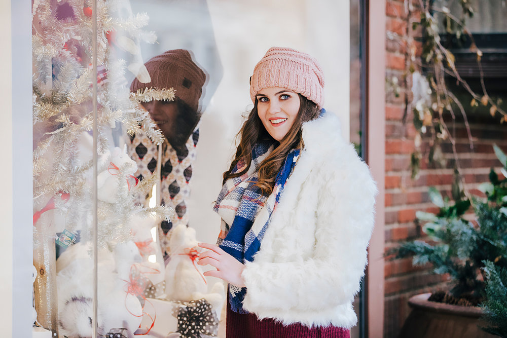 High school senior girl wearing pink hat and white coat standing in front of shop in downtown Oklahoma City by Amanda Lynn Photography.