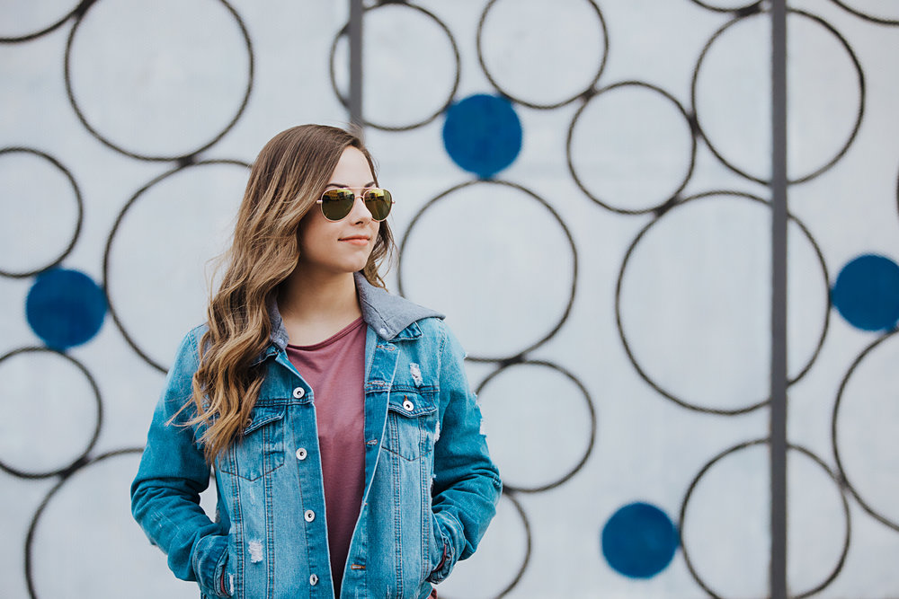 High school senior girl wearing jean jacket and sunglasses, looking of to the distance in automobile alley by Amanda Lynn Photography in Oklahoma City, Oklahoma.